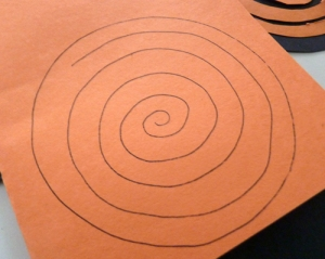 Draw a spiral slightly smaller than the black circles you cut out.